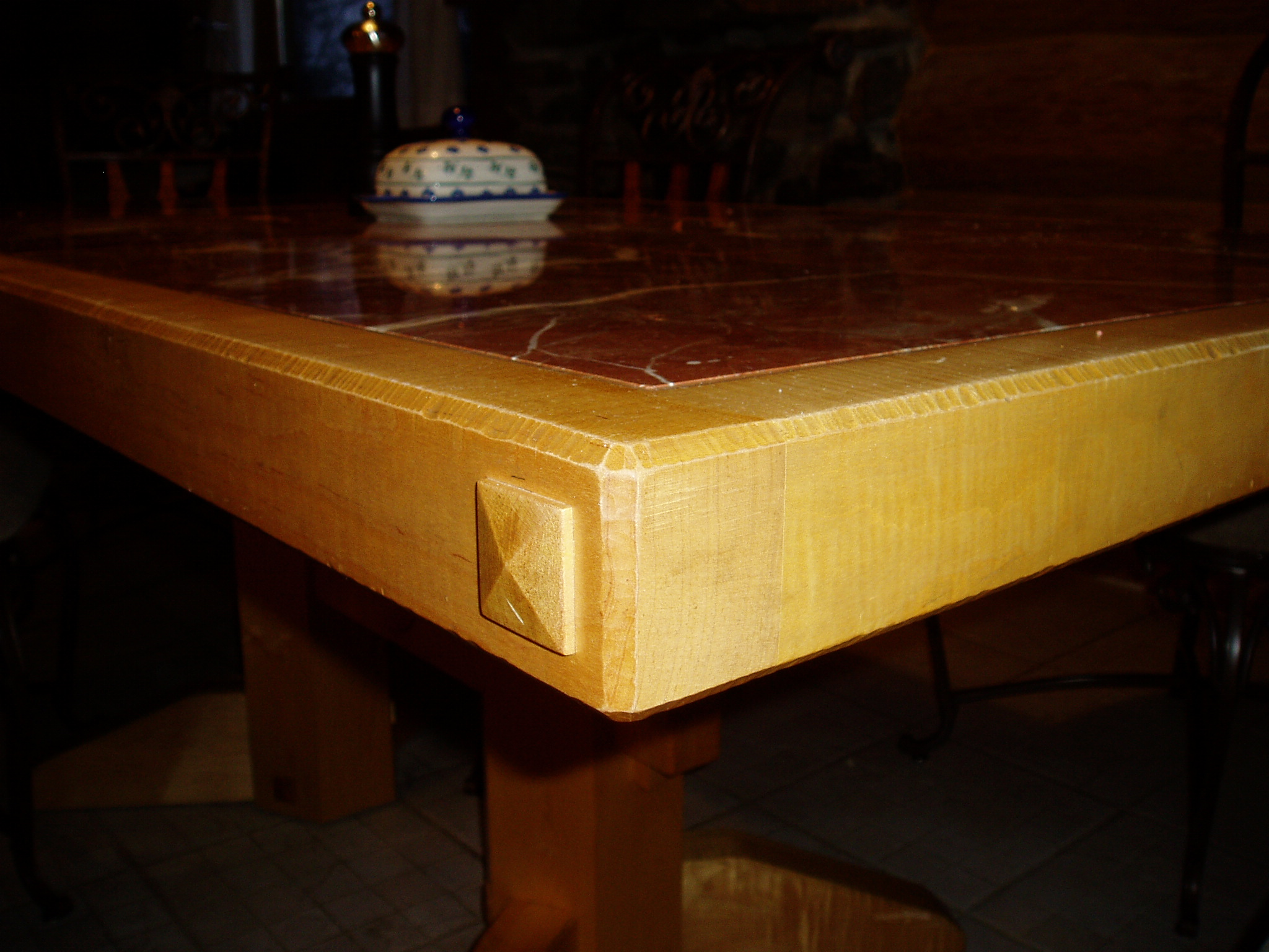 Heavy dining table made of Curly Maple with marble tiled top.
